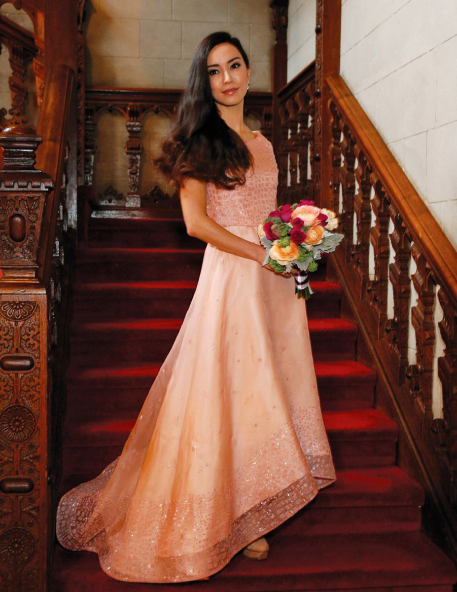 bridesmaid with flowers on red staircase wood bannister