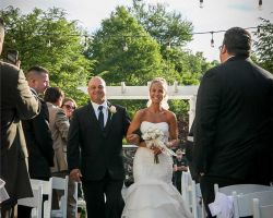 002-bride-smiling-walking-down-outdoor-wedding-ceremony-aisle