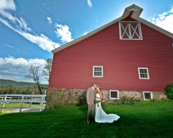 007-bride-and-groom-kiss-in-front-of-rustic-barn