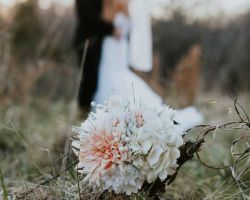 bouquet-in-front-of-bride-groom-in-field
