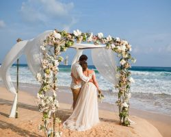 bride-groom-hugging-onbeach-looking-at-ocean