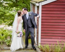 bride-groom-kiss-wedding-venue-barn-red-millrace-pond-scenic-rustic