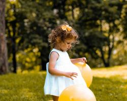 cute-flower-girl-with-balloons-wedding-venue-field